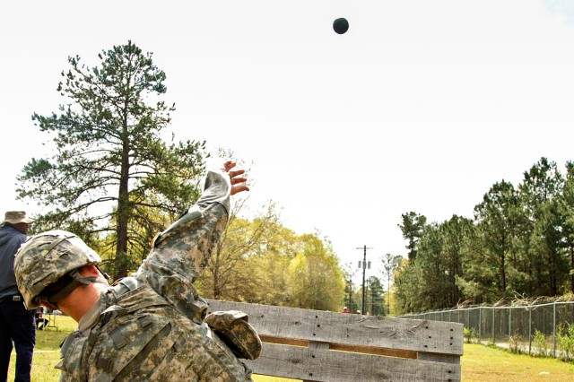 A Soldier at Fort. Benning throws a prototype, inert grenade from the kneeling position.