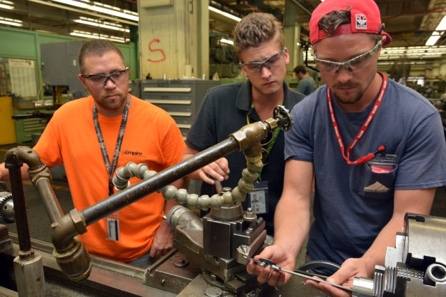 From left:  1st year apprentices Todd Herold and Corey LaBounty watch fellow apprentice Taylor Lee preparing to machine his first part.