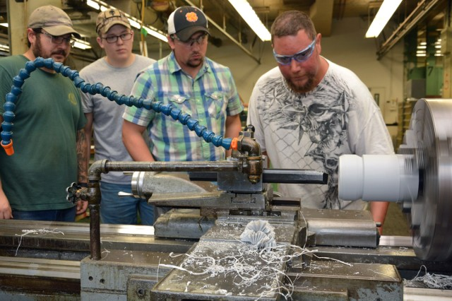 2nd year apprentice, Anthony Dudwoire, right, setting up a lathe for first year apprentices.