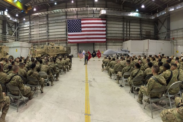 Secretary of the Army Eric Fanning addresses  Soldiers and civilians from U.S. Forces Afghanistan, including 1st Cavalry Division, at Bagram Airfield, Sept. 16, with a Mine Resistant Ambush Protected Vehicle and an Unmanned Aerial Surveillance drone behind him.