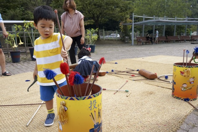 "A child picks up a stick to play a Korean traditional game, ""Tuho,"" at the Cheongju Children's Center, Choengju, South Korea, on September 14. Tuho is a game where people throw arrows into a quiver. The Cheongju Children's Center set up a playground for children to experience Korean traditional games. (U.S. Army photo by Cpl. Dasol Choi, 1st Armored Brigade Combat Team Public Affairs, 1st Cav. Div.)"