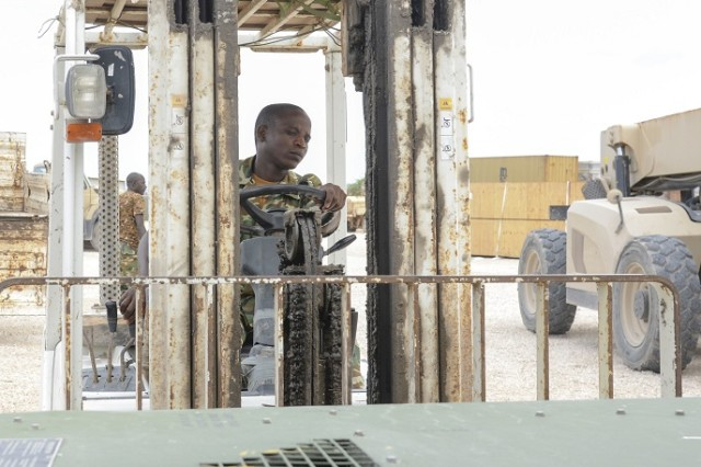 Burundi National Defense Force Cpl. Emmanuel, African Union Mission in Somalia Burundi contingent, uses a forklift to load a power generator onto a truck in Mogadishu, Somalia, Sept. 12, 2016. Burundi forces received more than 10 power generators, tires and spare parts for Mine Resistant Ambush Protected vehicles to remedy the wear and tear on vehicle parts caused by rough and uneven terrain. The MRAP vehicles are vital to keeping AMISOM forces safe from roadside bombs planted by al-Shabaab throughout Somalia. (U.S. Air Force photo by Staff Sgt. Benjamin Raughton)