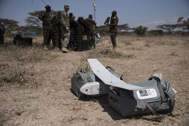 U.S. Army Staff Sgt. Charles Wirks, 1st Battalion, 124th Infantry Regiment and Raven master trainer, and members of the Kenyan Defense Force Military Intelligence Battalion, set up a computer system in preparation to fly the AeroVironment RQ-11 Raven, an unmanned aerial vehicle, Sept. 13, 2016, at a Kenyan training facility. U.S. Army Soldiers from the 1/124th Inf. Rgt., assigned to Combined Joint Task Force-Horn of Africa, provided basic training on assembly, disassembly, repair, and preventative maintenance in regard to basic mission planning and advanced flight plans for the Raven. (U.S. Air Force photo by Staff Sgt. Tiffany DeNault)