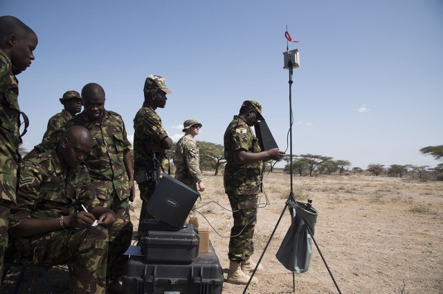 U.S. Army Staff Sgt. Charles Wirks, 1st Battalion, 124th Infantry Regiment and Raven master trainer, and members of the Kenyan Defense Force Military Intelligence Battalion, use an imagery system to fly the AeroVironment RQ-11 Raven, an unmanned aerial vehicle, Sept. 13, 2016, at a Kenyan training facility. U.S. Army Soldiers from the 1/124th Inf. Rgt., assigned to Combined Joint Task Force-Horn of Africa, provided basic training on assembly, disassembly, repair, and preventative maintenance in regard to basic mission planning and advanced flight plans for the Raven. (U.S. Air Force photo by Staff Sgt. Tiffany DeNault)