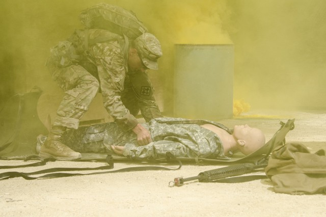 Surrounded by smoke Sergeant David I. Hull prepares a manikin, serving as an injured Soldier, onto a litter for medical evacuation (MEDIVAC) transport. The MEDIVAC lane was one of the competition exercises at the AMEDDC&S Best medic Competition.