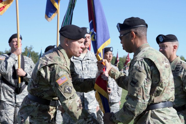 Brig. Gen. Aaron T. Walter, incoming commander of the 100th Training Division Operations Support, accepts the division's colors from the Commanding General of the 80th Training Command (TASS), Maj. Gen. A.C. Roper, during a change of command ceremony at Brooks Parade Field Fort Knox, Ky., Sept. 11, 2016.