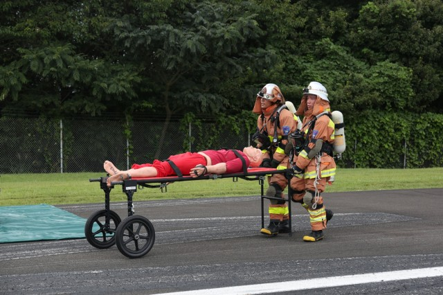 First responders transport an injured victim replica for treatment on the scene of the helicopter crash scenario for the full-scale exercise held Sept. 12-16 on Camp Zama. (U.S. Army photo by Lance D. Davis)