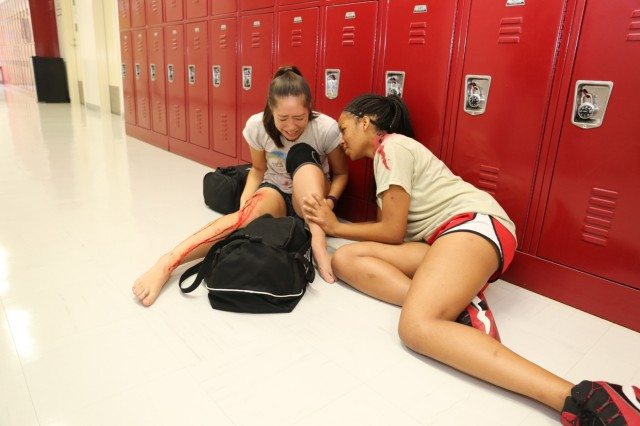 Taylor Seaman; left, senior at ZAHS, and Asia Jacob; right, sophomore at ZAHS, participate as wounded victims in the active shooter scenario for the full-scale exercise held Sept. 12-16 on Camp Zama. (U.S. Army photo by Lance D. Davis)