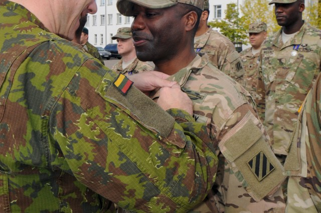 "RUKLA, Lithuania -- Col. Mindaugas Steponavicius, commander of the Lithuanian Armed Forces ""Iron Wolf"" Mechanized Infantry Brigade, pins a Lithuanian Armed Forces Medal for Mutual Support on 1st Sgt. Curtis Reid's chest during a ceremony Sept. 21. Reid, the first sergeant of Battle Company, 3rd Combined Arms Battalion, 69th Armored Regiment, 3rd Infantry Division, and the rest of his Solders received the medals from the Lithuanian Armed Forces for the training they conducted over the last six months with the Lithuanian Army. 3-69 AR has spent the last several months training in Lithuania in support of Operation Atlantic Resolve, a U.S. led effort being conducted in Eastern Europe to demonstrate U.S. commitment to the collective security of NATO and dedication to enduring peace and stability in the region."
