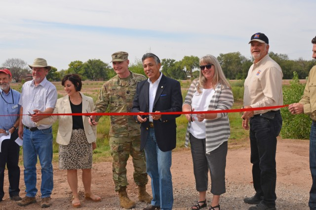 ALBUQUERQUE, N.M. -- AMAFCA engineer Nolan Bennet (far right) holds the ribbon that (l-r): AMAFCA director Bruce Thomson; MRGCD director John Kelly; Rio Grande High School principal Amanda De Bell; Albuquerque District Commander Lt. Col. James Booth; Bernalillo County Commissioner Art De la Cruz; AMAFCA director Debbie Stover; and MRGCD chief engineer Mike Hamman prepare to cut, officially opening Pond 187, Sept. 20, 2016.