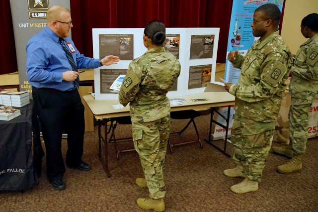 Soldiers gather information at booths set up at the 593rd Sustainment Command (Expeditionary) Care for 22 Suicide Stand Down Day Resiliency Expo at the Lewis North Chapel, Joint Base Lewis-McChord Sep 22.