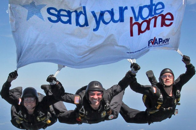 Members of the Army's Golden Knights parachute team pass on the Federal Voting Assistance Program's message for U.S. military and overseas citizens to submit their absentee ballots in time for the upcoming general election.