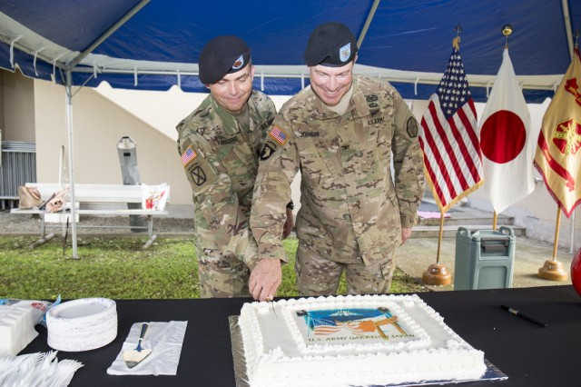 Col. William Johnson, commander of USAG Japan and incoming USAG Japan command sergeant major Command Sgt. Maj. Will Holland, cut the cake as part of the change of responsibility ceremony Sept. 26 at Camp Zama Yano Field.   (U.S. Army photo by Alia Naffouj)