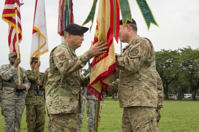 Col. William Johnson, commander of USAG Japan, passes the guidon to the new USAG Japan command sergeant major, Command Sgt. Maj. Will Holland, during the change of responsibility ceremony Sept. 26 at Camp Zama Yano Field.  (U.S. Army photo by Alia Naffouj)