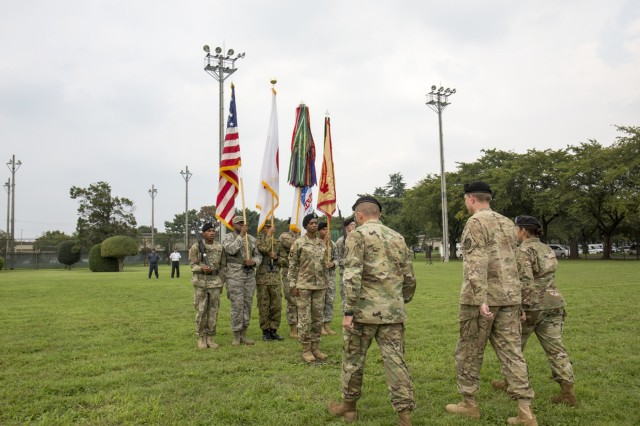 Col. William Johnson, commander of USAG Japan, Command Sgt. Maj. Rosalba Dumont-Carrion, outgoing command sergeant major and incoming command sergeant major, Command Sgt. Maj. Will Holland approach the color guard for the hand off of the USAG Japan guidon - an Army tradition to symbolize the change of responsibility - during the change of responsibility ceremony Sept. 26 at Camp Zama Yano Field.  (U.S. Army photo by Alia Naffouj)