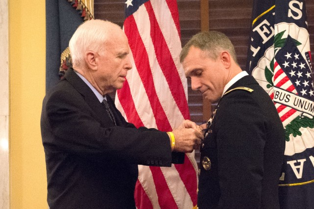 Sen. John McCain pins a Soldier's Medal on Lt. Col. David P. Diamond for saving lives at the Boston Marathon three years ago. The medal was presented during a ceremony on Capitol Hill, Sept. 27, 2016.