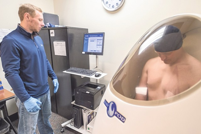 Michael Blair, Army Wellness Center health educator, performs body composition testing on Family member Brady Lewis using a BodPod. The BodPod uses air displacement and volume to tell clients what their lean and fat mass is and has less than a 1 percent margin of error.
