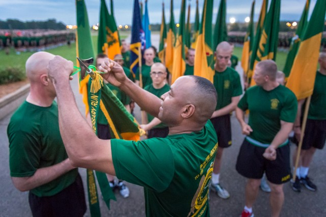 Brig. Gen. Kevin Vereen, chief, Military Police Regiment and MP School commandant, ties a 75th Anniversary Run streamer on a brigade guidon following the Regimental Run Monday.