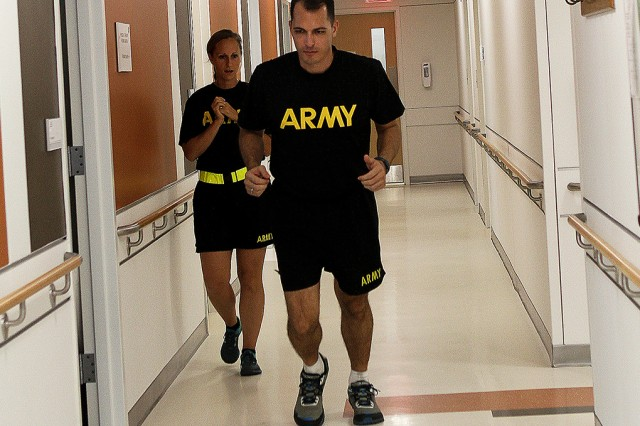 Maj. Eliza Szymanek, therapist, helps Maj. Daniel Caffarel, Behaviorial Sciences and Leadership Department instructor, on his running form during one of the running clinics at Keller Army Community Hospital Physical Thearpy Department Sept. 15. The clinic is designed to improve runners' techniques to reduce pain and prevent injuries. Here, Szymanek is instructing Caffarel to keep his arms close to his sides and to lean forward when running.