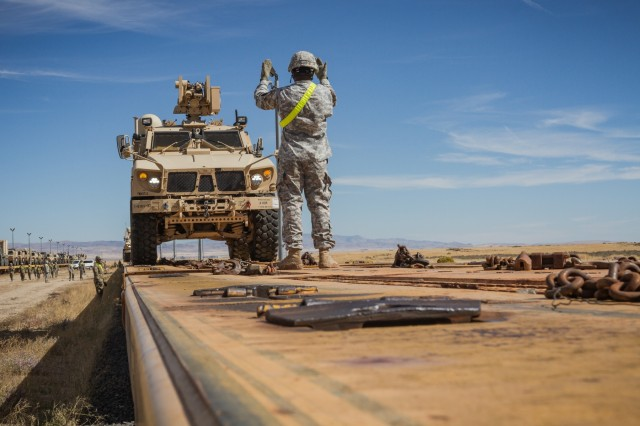 A U.S. Army Soldier assigned to 1st Battalion, 37th Field Artillery Regiment, 2nd Infantry Division Artillery guides a mine-resistant, ambush- protected vehicle during rail offload at Orchard Combat Training Center, Idaho, Sept. 25, 2016. The 200 pieces of equipment that arrived on the train will be used for Raptor Fury, a month-long training exercise to validate the mission readiness of 16th Combat Aviation Brigade with support from nearly 1,500 7th Infantry Division Soldiers.