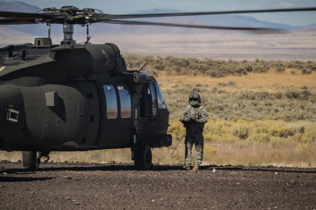A U.S. Army UH-60M Black Hawk helicopter crew chief assigned to 2nd Battalion, 158th Aviation Regiment, 16th Combat Aviation Brigade, 7th Infantry Division, communicates with pilots after landing at Orchard Combat Training Center, Idaho, Sept. 27, 2016. The aircraft will be part of Raptor Fury, a month-long exercise to validate 16th CAB's mission readiness with the support of nearly 1,500 7th ID Soldiers.