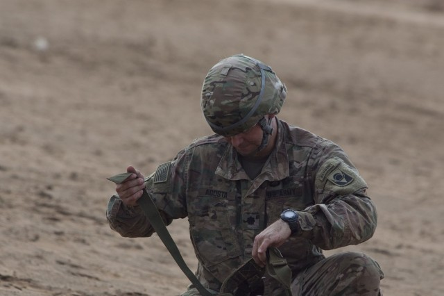 U.S. Army Lt. Col. Julio Acosta, 1st Battalion, 124th Infantry Regiment commander, repacks his parachute after landing on the designated drop zone Sept. 29, 2016, in Djibouti. U.S., French and Djiboutian airborne forces celebrated with a static line and high altitude low opening jump toward a designated drop zone. St. Michel is the patron saint of paratroopers, and the day included a celebratory mass and American jumpers being awarded French jump wings. (U.S. Air Force photo by Staff Sgt. Eric Summers Jr.)