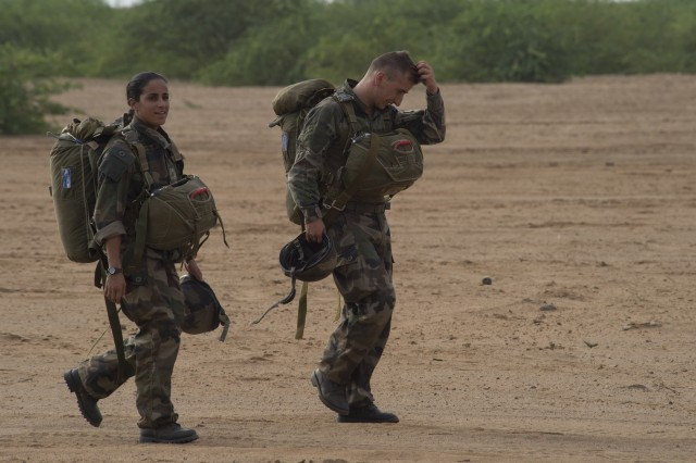 Two French airborne soldiers clear the drop zone after a static line jump from a C-160 Transall in celebration of St. Michel's Day Sept. 29, 2016, at Djibouti. U.S., French and Djiboutian airborne forces celebrated with a static line and high altitude low opening jump toward a designated drop zone. St. Michel is the patron saint of paratroopers, and the day included a celebratory mass and American jumpers being awarded French jump wings. (U.S. Air Force photo by Staff Sgt. Eric Summers Jr.)