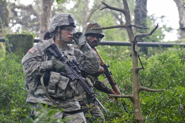 A U.S. Soldier with 5-20th Infantry Regiment, 1-2 Stryker Brigade, and his Indian counterpart move through an improvised explosive device detection course Sept. 17, 2016, at Chaubattia Military Station, India. This was part of Yudh Abhyas 2016, a bilateral training exercise geared toward enhancing cooperation and coordination between the two nations through training and cultural exchanges.