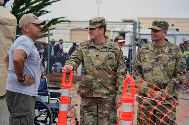 Tony Virrueta (left), a volunteer at the Veteran's Transition Center Stand Down, speaks with Col. Lawrence Brown (center), Presidio of Monterey commander, and Presidio Command Sgt. Maj. Roberto Marshall, Aug. 19.