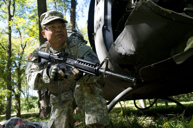 Army Sgt. Abon Jeadrik, an observer coach/trainer with 2nd Battalion, 410th Brigade Support Battalion, 177th Armored Brigade, reacts to contact during a mock casualty event as part of the first-quarter 2017 First Army Division East Best Warrior Competition at Camp Atterbury, Ind., Sept. 27, 2016. (U.S. Army photo by Staff Sgt. Darron Salzer, First Army Division East Public Affairs)