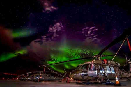 The Aurora Borealis shimmering above UH-60 Black Hawk helicopters. The Northern Lights are just one facet of what makes service in magnificent Alaska so unique.