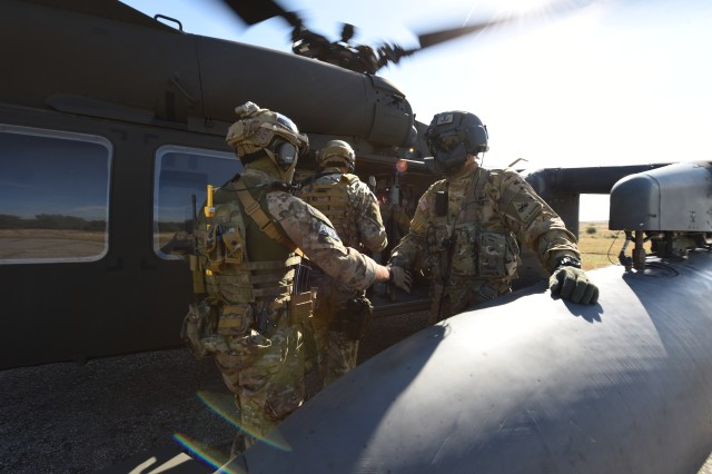 A Soldier from Charlie Company, 3rd Battalion, 501st Aviation Regiment, 1st Armored Division, Combat Aviation Brigade welcomes a Hungarian Special Forces Operator onto a UH-60 Black Hawk Helicopter during exercise Black Swan, near Veszprem, Hungary, Sept., 29, 2016.  Black Swan 16 is a multi-national special operations training exercise involving Soldiers from Slovakia, Croatia, Hungary, Poland and the United States.