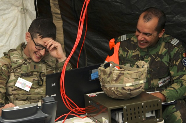 1st Lt. White, an air defense artillery officer with the 5th Battalion, 7th Air Defense Artillery Regiment, laughs with Lt. Col. Ladeiro, one of the exercise evaluators during Tobruq Legacy 16. Tobruq Legacy is an annual multinational air defense exercise designed to increase the interoperability of allied nations in Europe both tactically and technically.