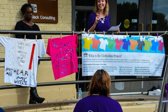 """Samantha Mathew, victim advocate, Rock Island Arsenal's Domestic Violence Victim Advocacy Program, reads a poem and tweets from domestic violence victims during her speech at the Rock Island Arsenal Post Exchange, following the """"Join the Fight"""" march, RIA, Oct. 6."""