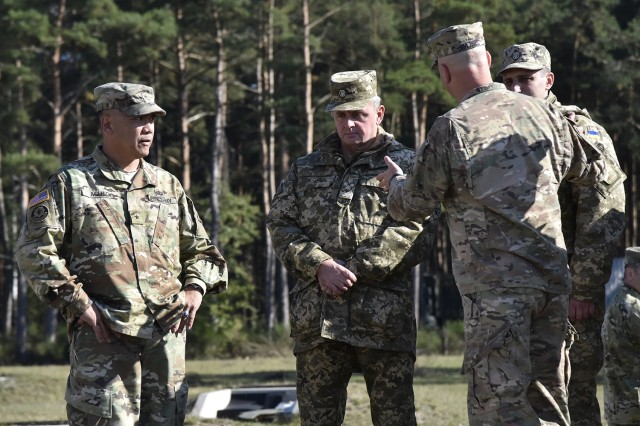 Brig. Gen. Tony Aguto (left), commander of 7th Army Training Command; Gen. Viktor Muzhenko, the chief of general staff, Commander in Chief of Armed Forces for Ukraine; and Lt. Col Oleksii Denysenko (right), interpreter for the General Directorate of Military Cooperation and Peacekeeping; listen as Col. Thomas Matsel, officer in charge of 7ATC's Operations and Plans division briefs on Range 118 in the Grafenwoehr Training Area, Oct. 10.