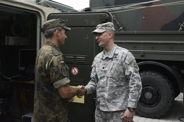 Lt. Col. Chris Keeshan, 102nd Signal Battalion commander, presents a commander's coin to a German BwCISCOM Soldier June 16, 2015 in Kastellaun, Germany