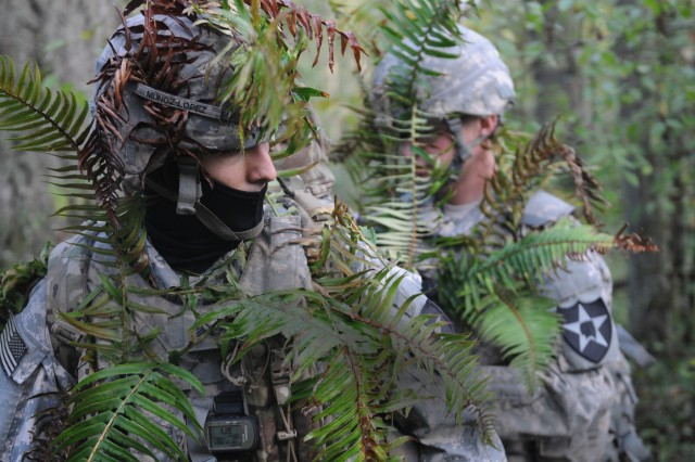 Spc. Spencer Secord, right, an intelligence analyst with the 2nd Infantry Division (ID), helps camouflage Sgt. Alfredo Munoz-Lopez, a cryptologic linguist, during a cyber-training exercise at Joint Base Lewis-McChord, Washington, in October 2015. Cyber, electronic warfare, survivability and PNT are critical technology focus areas for the new Army Rapid Capabilities Office. (U.S. Army photo by Capt. Meredith Mathis, 2nd Stryker Brigade Combat Team, 2nd ID)