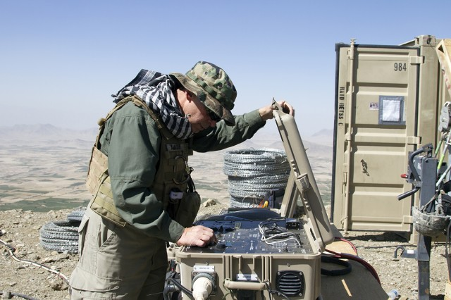Joseph Amadee, REF operational lead, configures power settings for a hybrid battery system that greatly reduces fuel consumption of the Rapid Aerostat Initial Deployment tower in Kabul, Afghanistan, in September 2014. The Army Rapid Capabilities Office's mission is complementary to that of the REF, which has a 180-day turnaround time and delivers a specific piece of kit to meet the urgent operational needs of a specific forward-deployed unit. (U.S. Army photo by Sgt. William White, International Security Assistance Force Joint Command)
