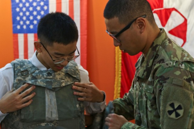 Pfc. Young Gyu Chun, assigned to the Eighth Army Public Affairs Office, helps a visitor to the Eighth Army Experience booth try on the Improved Outer Tactical Vest at the ROK Ground Forces Festival in Gyeryong, Oct. 2. The Eighth Army booth was part of the U.S. contingent at the festival which included Soldiers and equipment from the 2nd Infantry Division (Now the 2nd Inf. Div./ROK-U.S. Combined Division), the 19th Expeditionary Sustainment Command and the 35th Air Defense Artillery Brigade, who all participated in the festival Oct. 2-6 to showcase the U.S. forces role in the ROK to festival attendees. The festival provides attendees a first-hand experience with both ROK and U.S. service members and draws crowds of more than 1 million visitors every year.