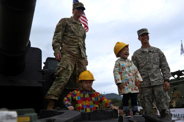 Staff Sgt. Nathan Brummer (left) and Pfc. Kenneth Woods (right), M109 Paladin crewmembers from 210th Field Artillery Brigade, 2nd Infantry Division (Now the 2nd Inf. Div./ROK-U.S. Combined Division), pose with children attending the ROK Ground Forces Festival, Oct. 2. The Paladin static display was part of the U.S. contingent at the festival which included Soldiers and equipment from the 2nd Infantry Division (Now the 2nd Inf. Div./ROK-U.S. Combined Division), the 19th Expeditionary Sustainment Command and the 35th Air Defense Artillery Brigade and the Eighth Army Experience booth run by the Eighth Army Public Affairs Office, who participated in the festival Oct. 2-6 to showcase the U.S. forces role in the ROK to festival attendees. The festival gives attendees a first-hand experience with both ROK and U.S. military members and draws crowds of more than 1 million visitors every year.