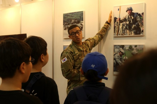 Pfc. Young Gyu Chun, assigned to the Eighth Army Public Affairs Office, explains a photo to a group of school children at the Eighth Army Experience booth at the ROK Ground Forces Festival in Gyeryong, Oct. 4. The Eighth Army booth was part of the U.S. contingent at the festival which also included Soldiers and equipment from the 2nd Infantry Division (Now the 2nd Inf. Div./ROK-U.S. Combined Division), the 19th Expeditionary Sustainment Command and the 35th Air Defense Artillery Brigade who participated in the festival Oct. 2-6 to showcase the U.S. forces role in the ROK to festival attendees. The festival gives attendees a first-hand experience with both ROK and U.S. military members and draws crowds of more than 1 million visitors every year.