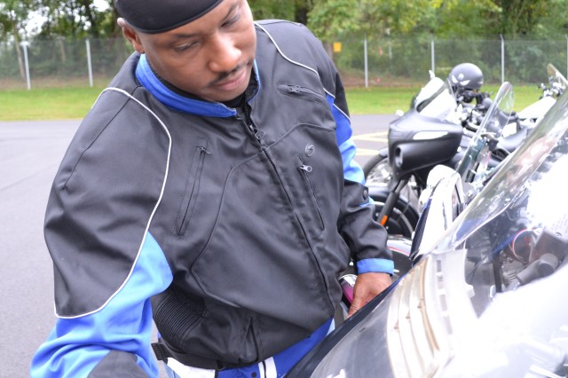 Master Sgt. Gregory Moody, contracting officer representative for the 80th Training Command (TASS), cleans his motorcycle at the command's Family Programs Center in Richmond, Va., as he prepares for the motorcycle mentorship ride in honor of Sgt. Scott McGinnis on Oct. 6, 2016. McGinnis, 22, died in a motorcycle accident July 4, 2016 in Centre, Ala., where he was struck by another vehicle.