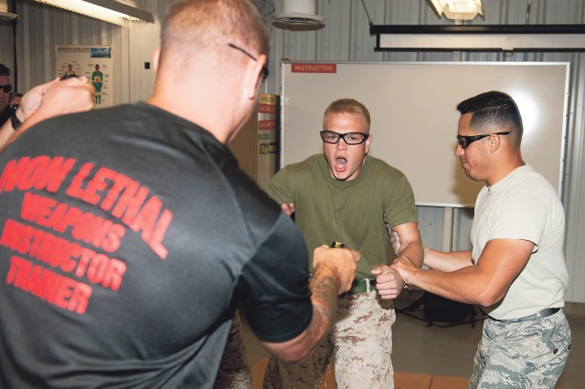 Marine Cpl. Mark McNulty, traffic investigator assigned to the Marine Corps Air Ground Combat Center, Twentynine Palms, Calif., is tased as part of the curriculum in the Department of Defense Inter-service Nonlethal Individual Weapons Instructor Course.