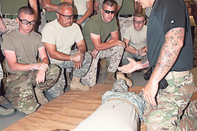 Staff Sgt. Rob McQueen, Department of Defense Inter-service Nonlethal Individual Weapons Instructor Course instructor, demonstrates the removal of the taser probes from the back of Sgt. 1st Class. William Peace, class leader, after he was tased.