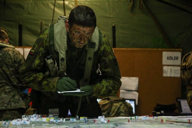 A Lithuanian soldier of the Mechanized Infantry Brigade Iron Wolf documents unit placements while managing a tactical operations center during Exercise Allied Spirit V at 7th Army Training Command's Hohenfels Training Area, Germany, Oct. 11, 2016. Exercise Allied Spirit includes about 2,520 participants from eight NATO nations, and exercises tactical interoperability and tests secure communications within Alliance members and partner nations.  (U.S. Army photo by Spc. Nathaniel Nichols)