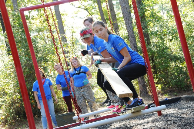 Participants work together to overcome an obstacle at the Leaders Reaction Course.