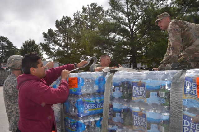 From left, Spc. Zachary McKenzie, Pvt. Raja Kahn, Sgt. Chris Trant, and Spc. Kevin Dandy, of the 690th Rapid Port Opening Element work together to strap down more than 500 cases of bottled water headed to Haiti as members of the 689th RPOE are already on site to provide humanitarian assistance in the wake of Hurricane Matthew.
