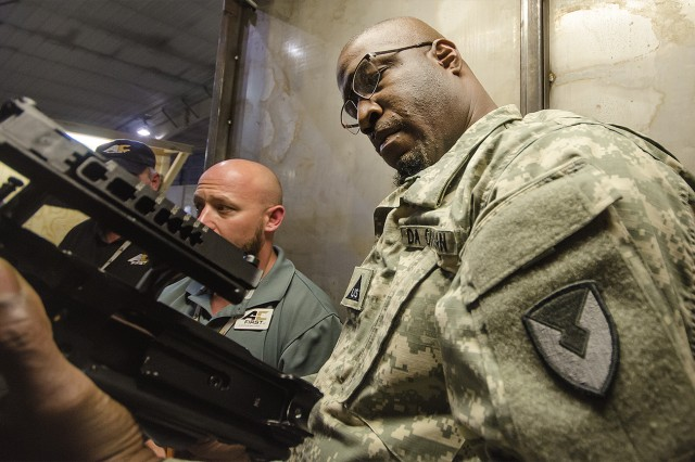 Aaron Anderson, quality assurance specialist, 401st Army Field Support Battalion-Afghanistan, examines a weapon during a QA inspection at Bagram Airfield, Afghanistan, Oct. 7. (U.S. Army Photo by Justin Graff, 401st AFSB Public Affairs)
