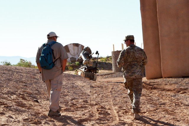 FORT BLISS, Texas - Sgt. 1st. Class Kyle R. Kinard, U.S. Army Training and Doctrine Command, capabilities manager for explosive ordnance disposal, walks with a project site manager as they assess the capabilities of the andros FX during the Army War Fighting Assessment or AWA 17.1 Oct. 14, at Fort Bliss Texas. AWA allows industry engineers to work side-by-side with Soldiers to rapidly correct and improve capabilities. (Photo by Staff Sgt. Cashmere Jefferson, 7th Mobile Public Affairs Detachment)