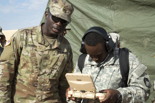 U.S. Army Sgt. Tsameye assists his Soldier, Pvt. Hartley, with navigating a TALON robot, at Fort Bliss, Tx., Oct. 13, 2016.  The robotics training was conducted as a part of the Army Warfighting Assessment (AWA) 17-1 to assess operational effectiveness. (U.S. Army photo by Spc. Tianna S. Wilson)